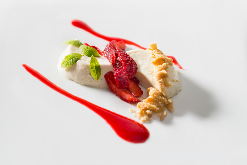 Verbeena panna cotta topped with strawberries, crumbled butter cookies, mint leaves and a rasberry coulis on a white rectangle plate prepared by Chef Kerry Heffernan