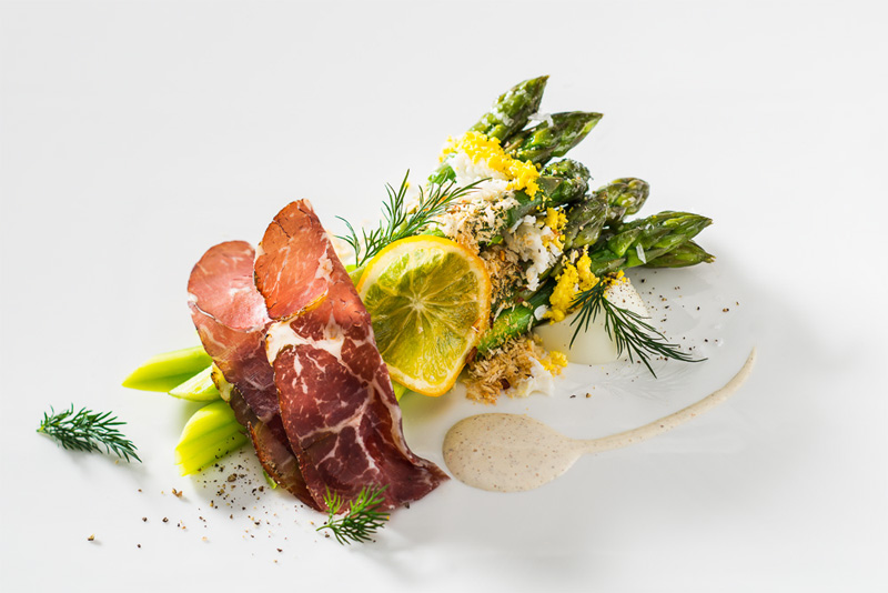 Asparagus topped with minced egg, air dried beef, butter fried panko, a slice of a meyer lemon, dill and cardamon vinaigrette on a white background prepared by Chef Kerry Heffernan