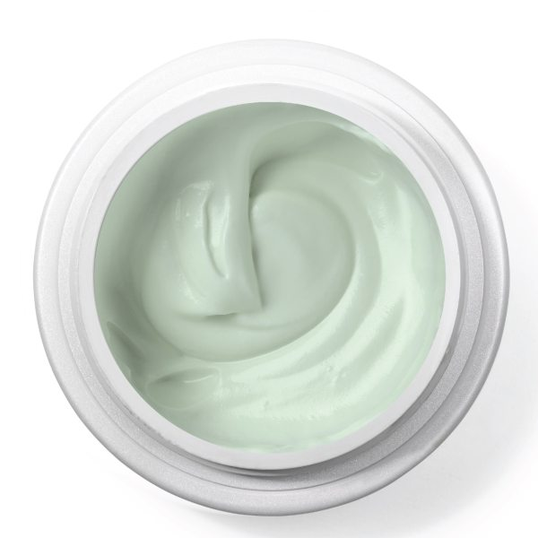 green cream in open jar on white background