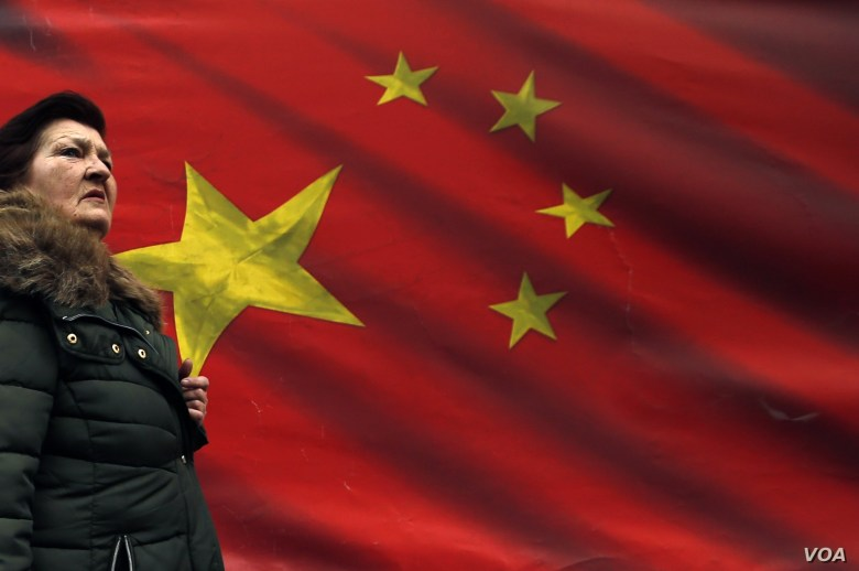 In this photo taken Friday, March 1, 2019, a woman walks by Chinese flag placed on a street in Belgrade, Serbia.