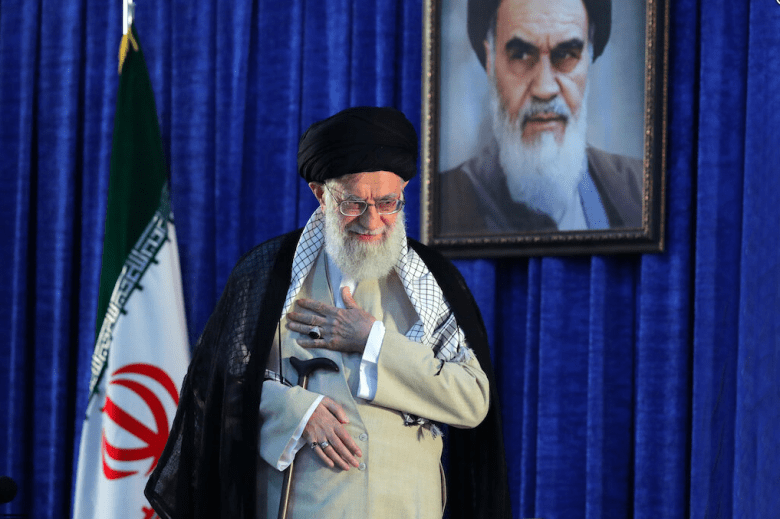 Iranian Supreme Leader Ayatollah Ali Khamenei gestures to a crowd at a June 4, 2019 ceremony in Tehran marking the 30th anniversary of the death of his predecessor, Ayatollah Ruhollah Khomeini, whose portrait appears behind him.