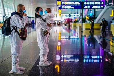 Travelers in protective suits are seen at Wuhan Tianhe International Airport in Wuhan