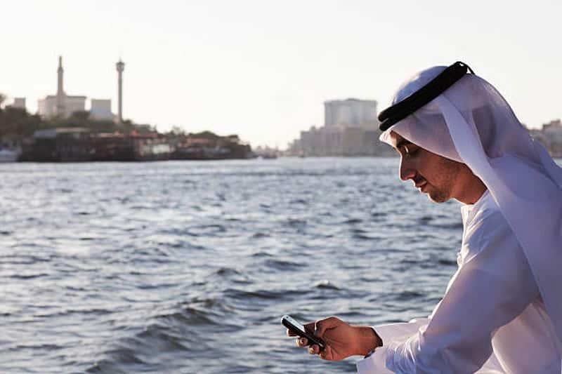 arab-businessman-using-phone-dubai-creek-picture