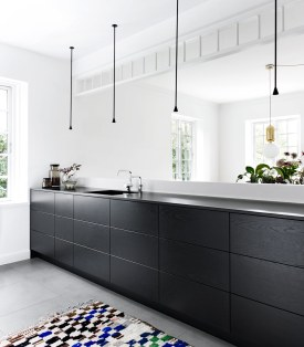 Fronterne i sortbejdset egefiner har synlig træstruktur, hvilket skaber et godt modspil til det rene look i det sort-hvide køkken.