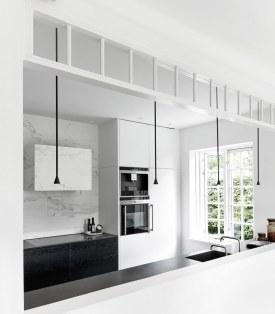 Køkkenelementernes møbelagtige udtryk, belysningen og den smarte glaskappe fra loftet skaber en elegant overgang mellem de to rum.