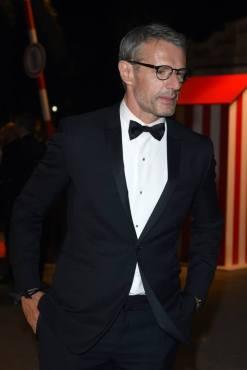 Lambert Wilson wearing a Dior Homme silk satin tuxedo, white cotton piqué front tuxedo shirt and a black silk bow tie with black leather derbies.