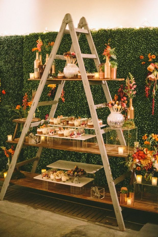 Miniature-desserts-displayed-on-a-step-ladder-with-faux-hedge-backdrop