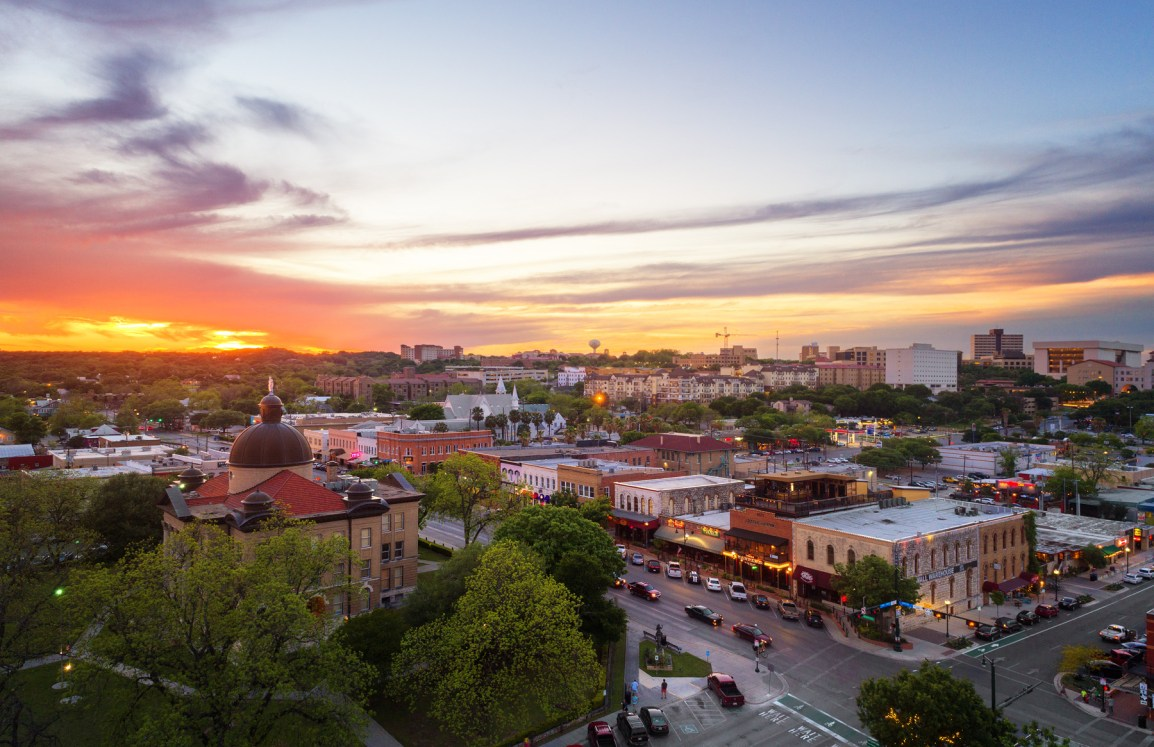 Aerial view of downtown San Marcos with Texas State University in the background at sunset.
