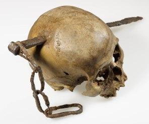 Schädel aus Boppard, mit einem seitlich durchgeschlagenem Eisendorn und Teile einer eisernen Kette.