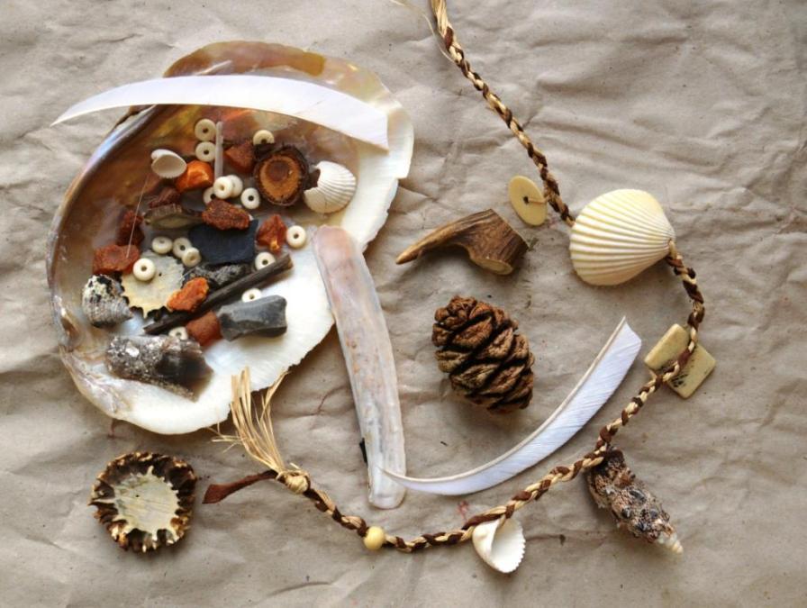 """In unserem Workshop """"Steinzeitamulett"""" können Kinder und Familien eine eigene Kette, Armbänder oder auch ein Amulett aus Naturmaterialien herstellen. Dazu werden Muscheln, Rinde, Bernstein und vieles mehr verwendet."""