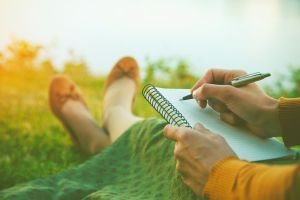 Woman ready to write with pen and notebook in hand