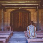 Seeking the pleasure of the Lord. Woman praying sitting on wooden bench pew.