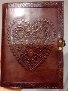 Red journal with celtic heart design to begin writing new chapters.