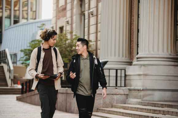multiracial male friends talking while walking down street