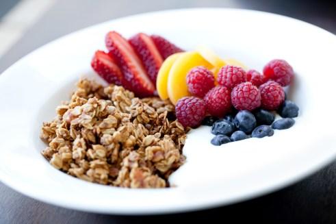 An elegant white bowl with granola, yogurt and fresh fruits