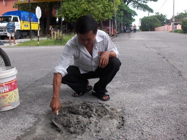 洪敦吉村长亲自把破洞铺平