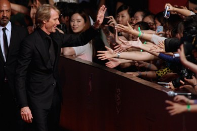 Hong Wu/Getty Images Director Michael Bay waves hand to fans attending the red carpet for the worldwide premiere screening.