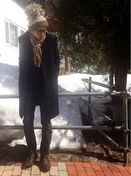 グレーのボンボンニット帽×黒のコート×ダークグレーのパンツ