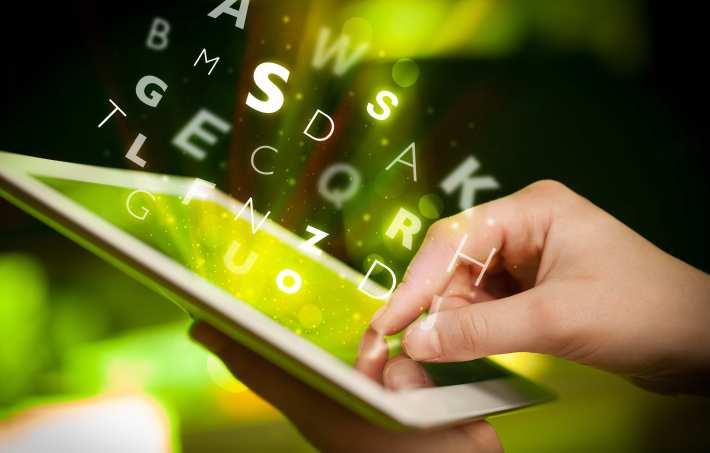doigt pointant une tablette d'ordinateur avec des lettres sortant de l'appareil — typographie