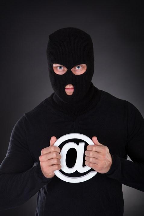 Pirate habillé en noir portant une cagoule avec un symbole de domaine Internet blanc à la main alors qu'il se tient dans l'obscurité, conceptuel de la sécurité en ligne et de la cybercriminalité