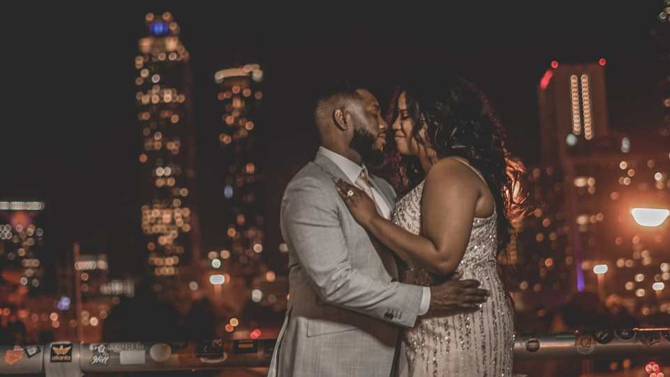 The couple kissing while overlooking the Jackson Street Bridge