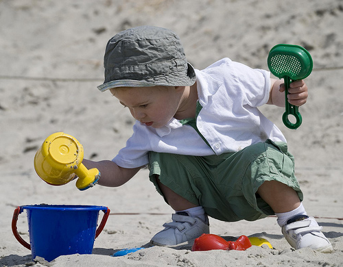Toddle playing in sand on the beach