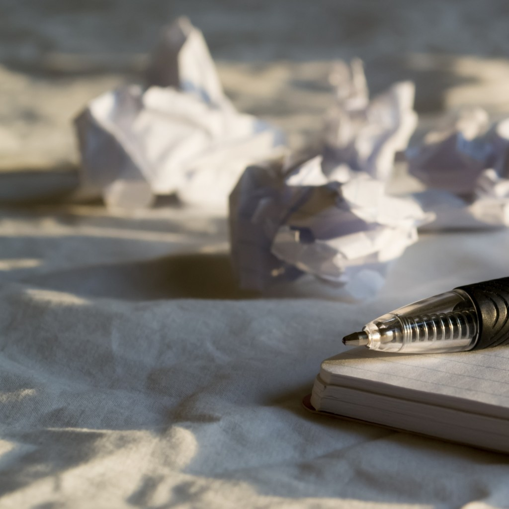 Image of crumpled papers and a pen representing the frustration of writer's block. But writer's block is not the end.