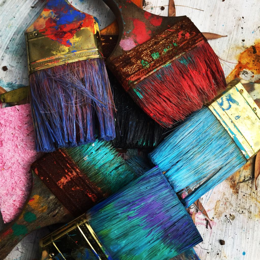 colorful paint brushes in a criss-crossing pile represent imagination, inspiration, and passion