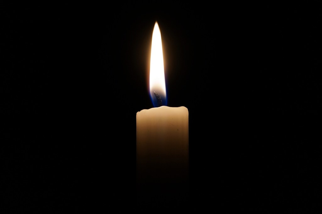 A pillar candle burning against a black background. Develop a personal ritual to care for yourself during difficult times.