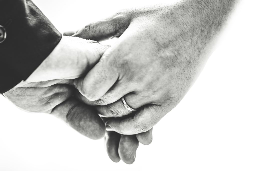 Image of a woman's hand holding a man's hand, an illustration for Friday Flash Fiction: For Better or Worse by Lynette M. Burrows