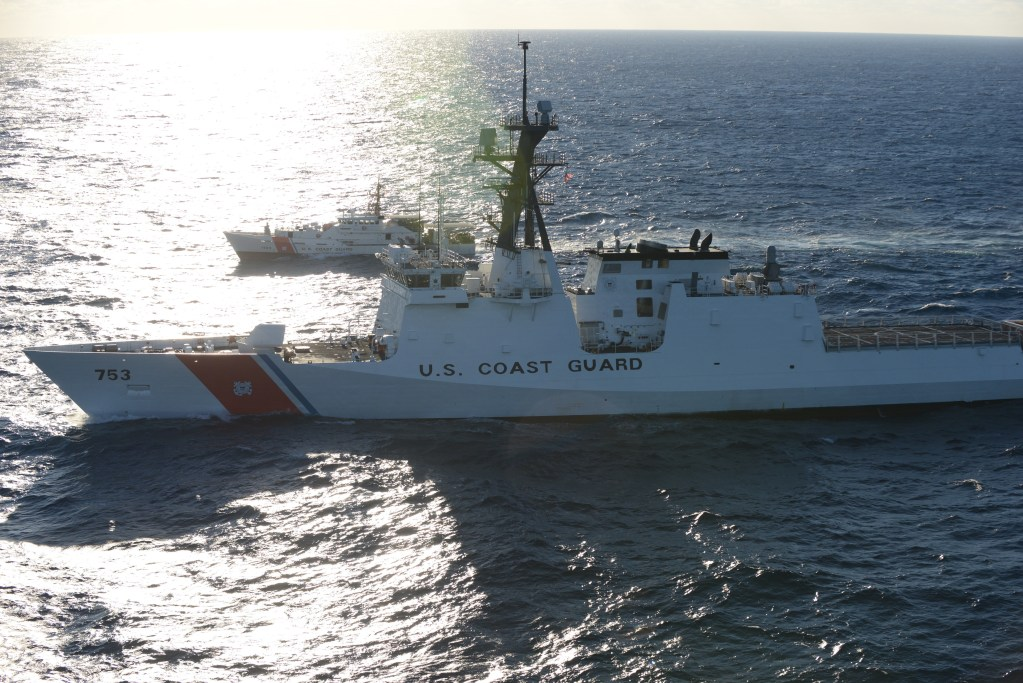 Image of a large Coast Guard cutter escorted by a smaller Coast Guard Cutter.