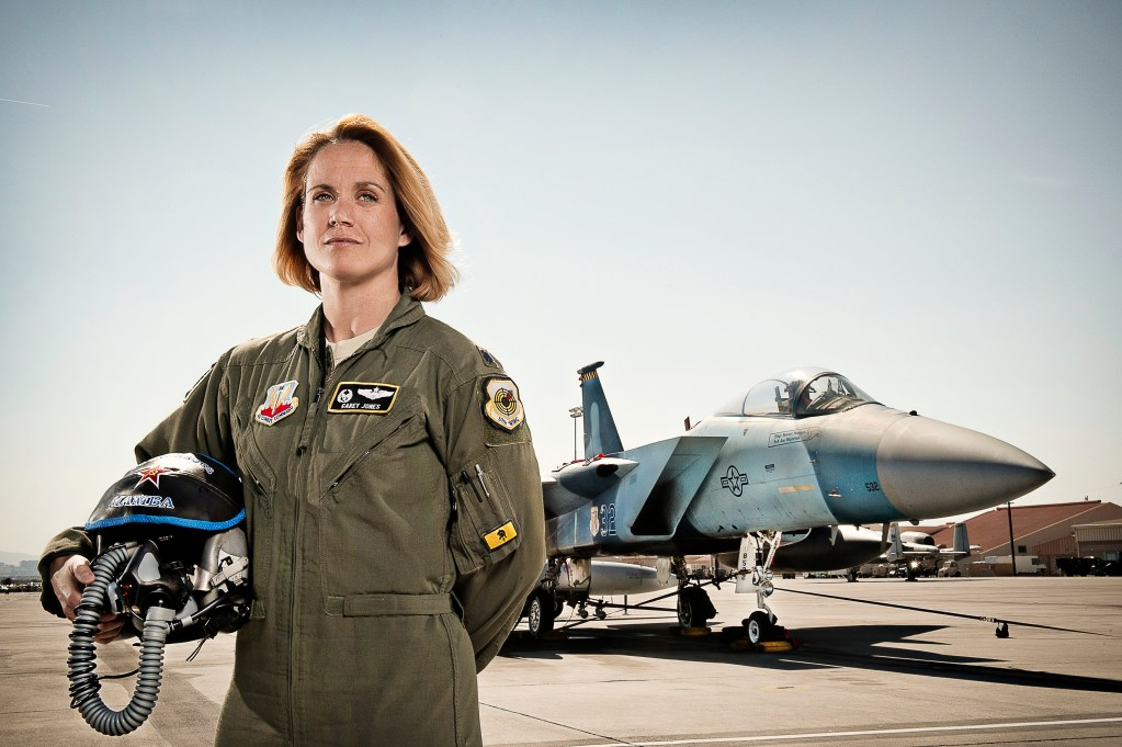 Image of uniformed Female Airman pilot in front of her plane
