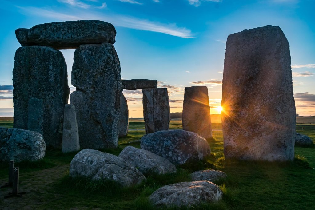 image of Stonehenge the the rising sun visible between two stones.