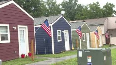 Image of a row of tiny homes flying American flags.