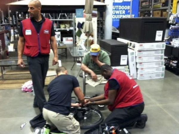 image of three hardware store employees fixing a broken wheelchair in the middle of the aisle.