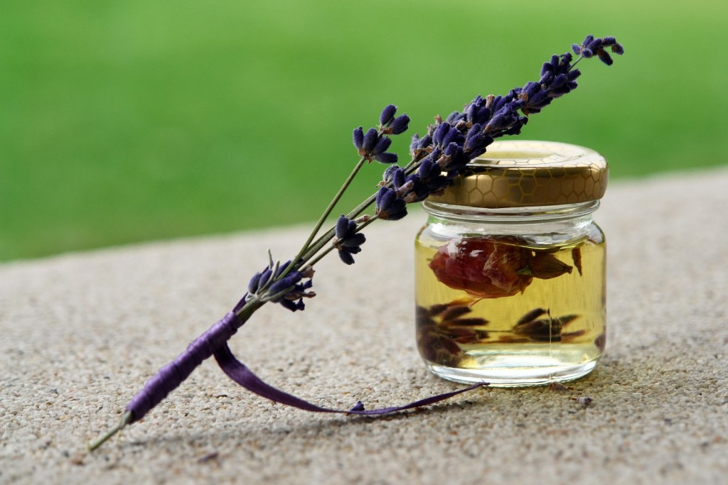 Image of a sprig of lavender and a bottle of essential oil, one way you can reduce your stress with a sniff