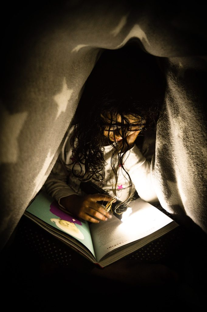 Girl reading under a blanket makes her own eighth day of the week.