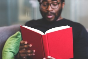 Black man reading a book with a red cover--does he know why these first lines work?