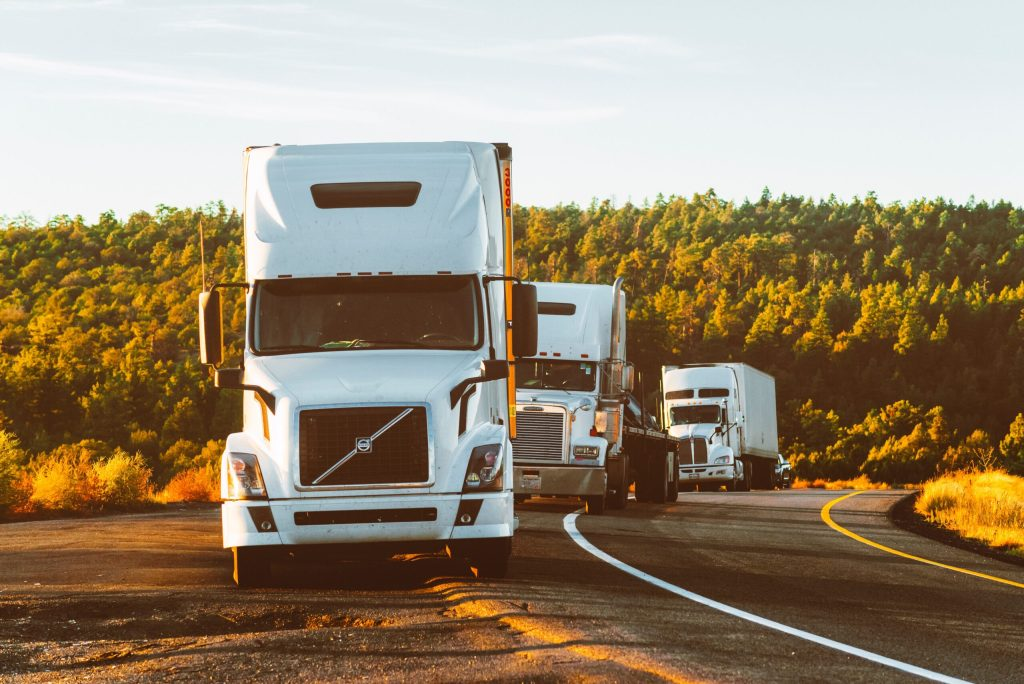 Three white semi-trailer trucks coming down the road toward you--in the future it may be a great big driverless convoy