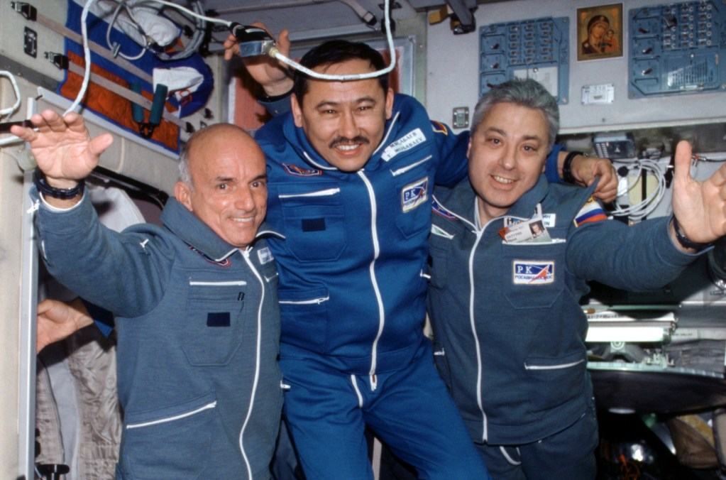 Image of three men onboard space station, one is the first private citizen ins space, would you be a space tourist