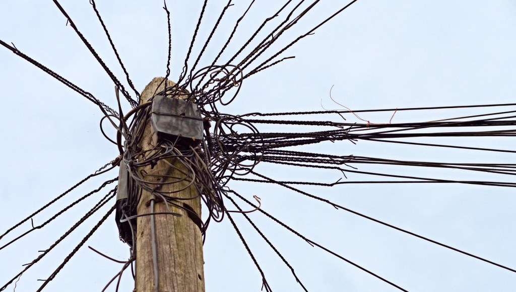 image is of the tangled and knotted top of a telephone pole with wires going every direction. If you feel knotted up you need to get away from it all.
