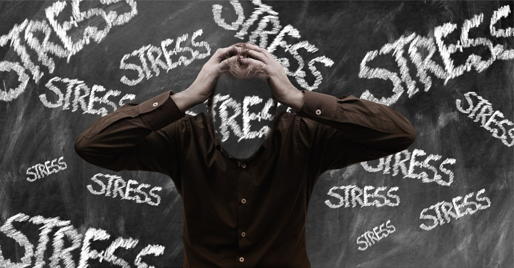 the word stress scatted across the scree and covering this woman's face symbolic of stress fatigue