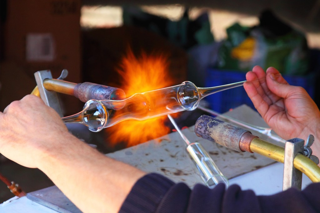 Image of hands holding a glass cylinder in front of a torch and stretching the glass--labor day inspirations and information