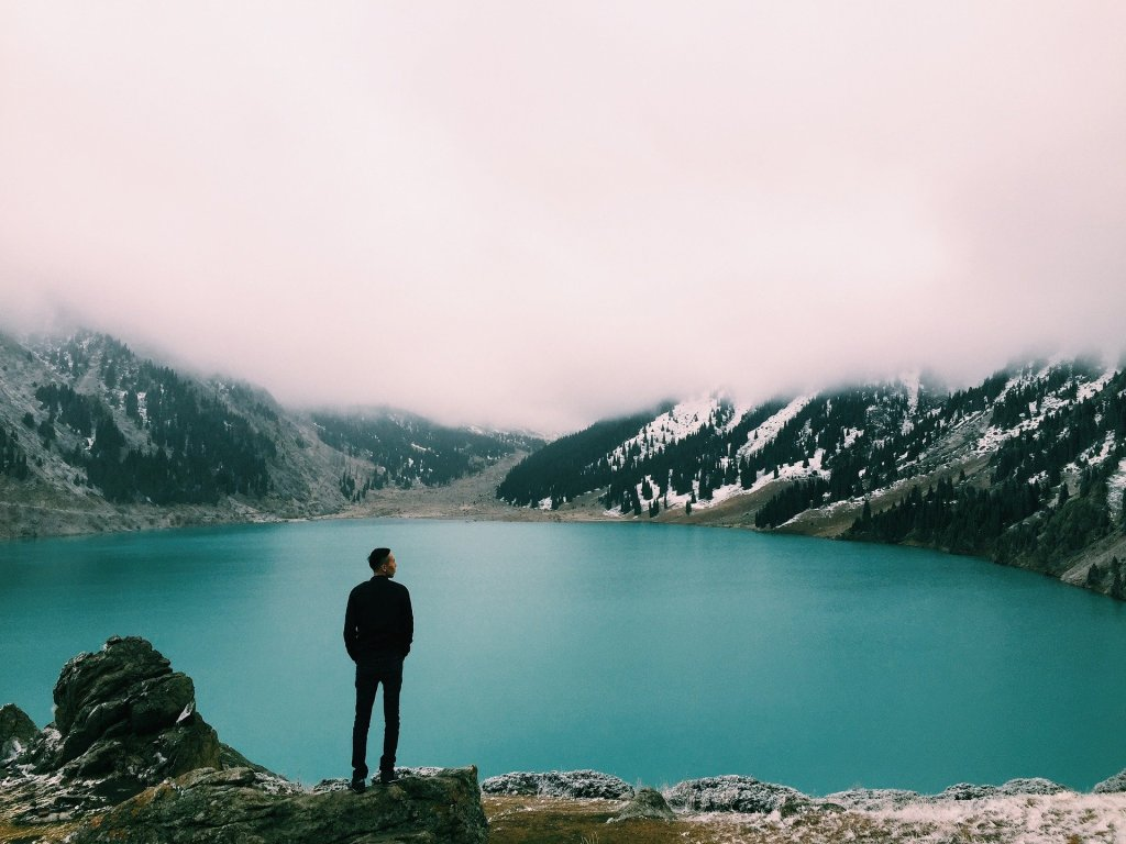 Image of a man silhouetted against a blue glacial lake with mountains and a pink sky in the background