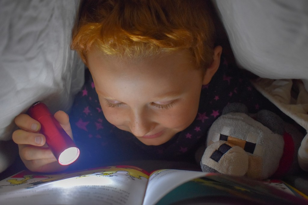 child reading by flashlight under the covers