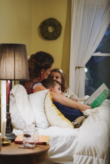 a woman sitting in bed, reading bedtime stories to her children