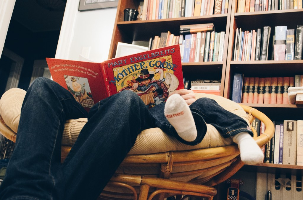 One reading style illustrated in this photo is a from the feet-up angle of a parent and child holding a Mother Goose book while sitting in a papa-san chair near a full bookshelf-what's your reading style?