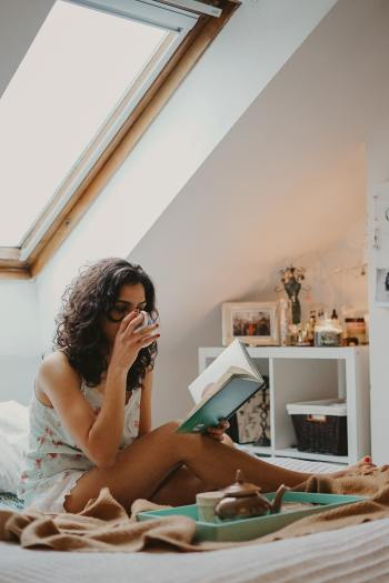 A woman seated on a bed under an attic window reading and drinking hot tea