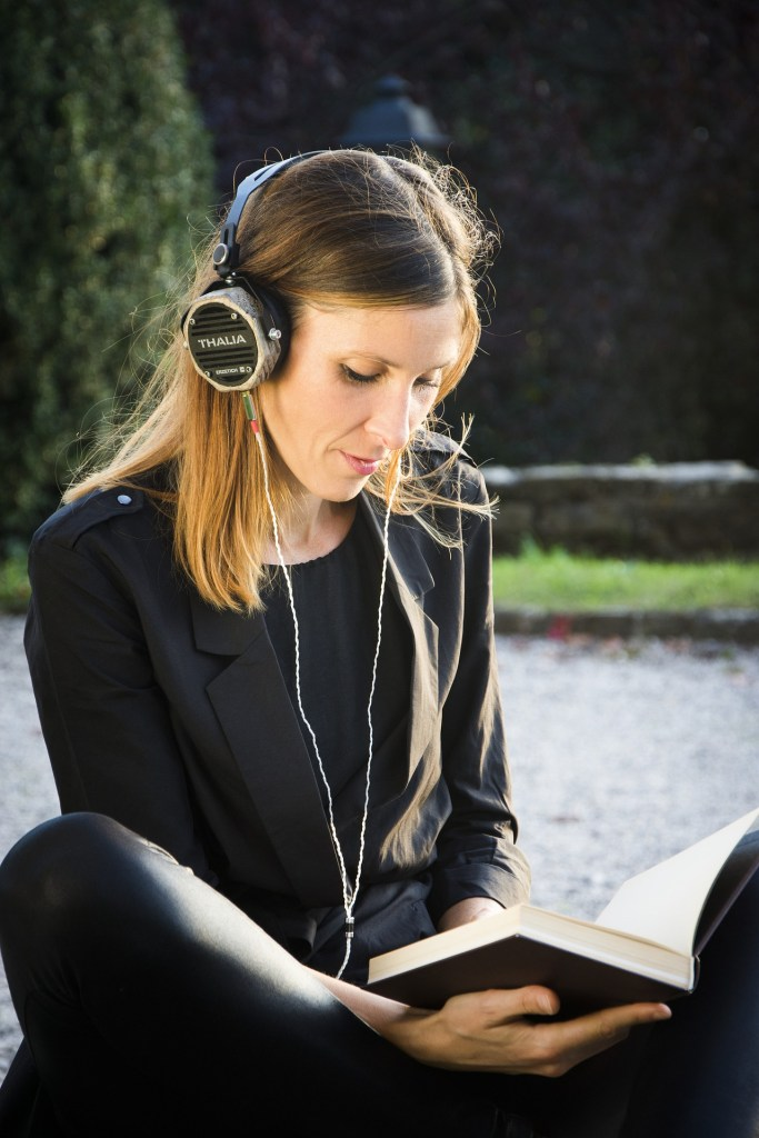 woman reading a book while wearing headphones. Try audiobooks is one of 12 ways to increase your reading pleasure