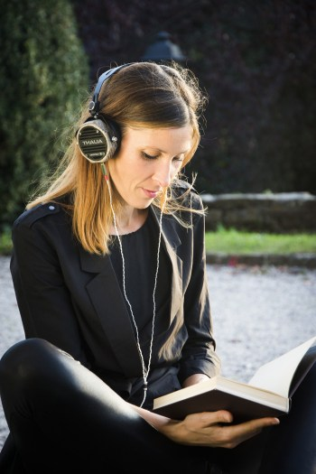 a woman seated cross-legged reading a book while wearing headphones